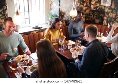 Group Of People Eating In Restaurant Of Busy Traditional English Pub