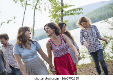 A group of people enjoying a leisurely walk by a lake.