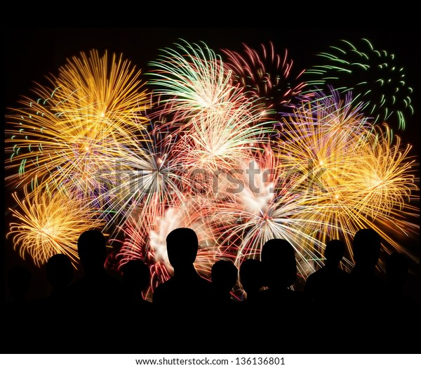 Group of people enjoying spectacular fireworks show in a carnival or holiday. People in silhouette.