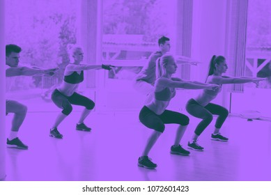 Group of people exercising at the gym and stretching duo tone