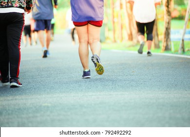 Group of people exercising in a park concept.photographed at the corner of the runner's foot.