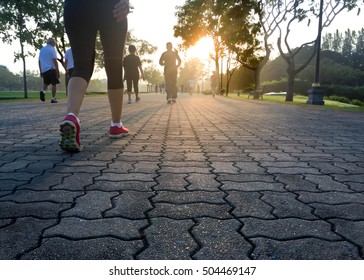 Group of people exercising in the park in sunrise morning well being concept