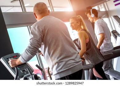 Group of people exercising together on treadmills in gym class