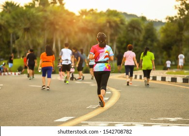 Group of people exercising  walking in the park in sunset evening, well being concept