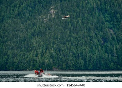 Group of people exploring an Alaskan fjord in a zodiac with a seaplane flying over them