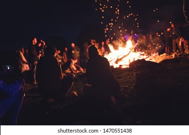 Group of people at the festival near camp fire with campfire song playing campfire games and eating camp fire grill, telling campfire stories near the fire with wood, flames in the nature at night
