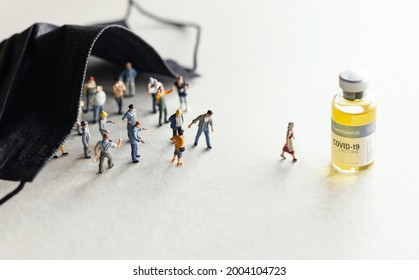 Group of people (figurine) standing and walking to the Coronavirus COVID-19 vaccine for injection .Coronavirus vaccine, population immunization campaign concept background.
