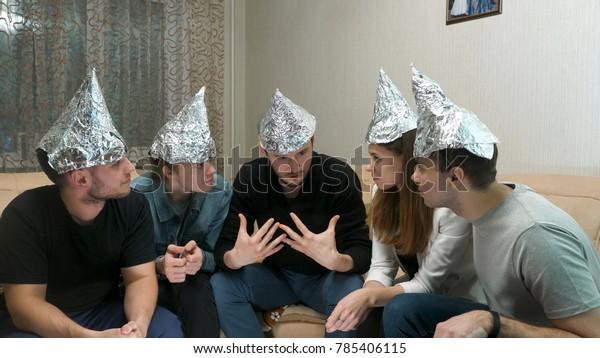 Gruppe von Leuten mit Folie auf dem Kopf diskutieren Verschwörungstheorien. Freunde mit Folie auf dem Kopf. Wissen Sie, sie können Ihren Geist nicht lesen