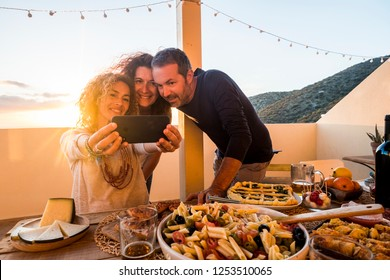 Group of people friednship concept have fun together taking selfie during a dinner or lunch outdoor at home in the terrace - firends and caucasian women and man eat and drink to celebrate