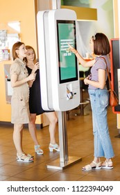 Group of people, friends ordering food at the touch screen self service terminal by the electronic menu in the fastfood restaurant