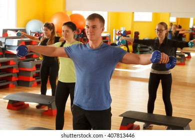 Group of people in the gym, exercising with dumbbells