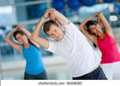 Group of people at the gym stretching their arms