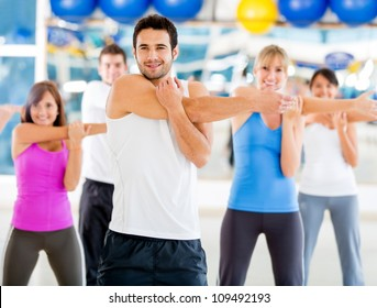Group of people at the gym stretching to warmup