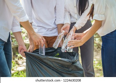 Group of People Hands putting recycling waste bit to Black garbage bag collection in park .Environmental CSR Corporate social responsibility concept .
