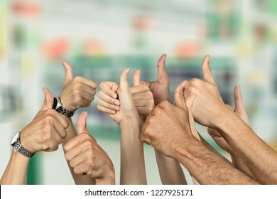Group of people hands showing thumbs up signs on background