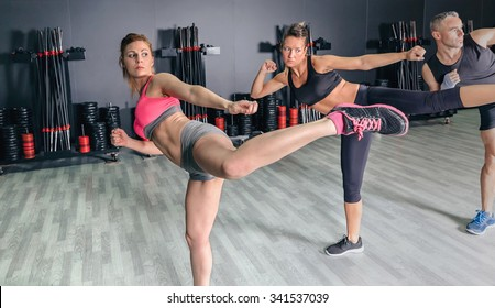 Group of people in a hard boxing class on gym training high kick