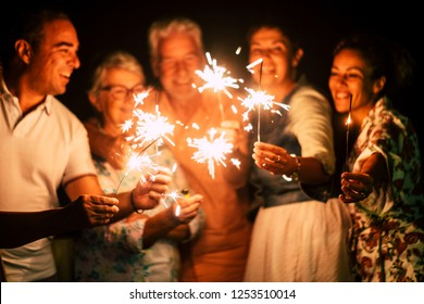 group of people have fun celebrating together new year eve or birthday with sparkles light and fireworks in friendship outdoor at evening time - family and friends different ages celebrate friendly
