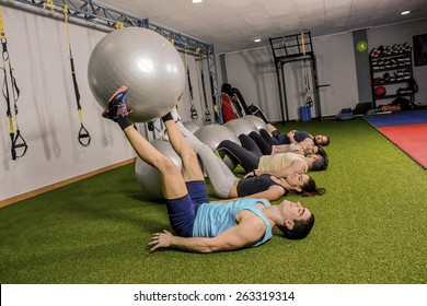 Group of people have fun training with balloon a gym
