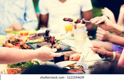 Group of people having BBQ party outdoors