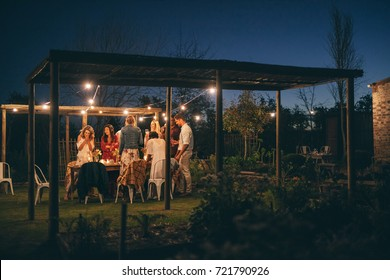 Group of people having a dinner party. Men and women standing around a table in garden restaurant .