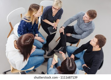 Group of people having a meeting together seated in a tight circle in a view from above