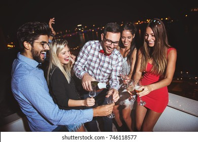 Group of people having a party on the roof, opening a champagne bottle