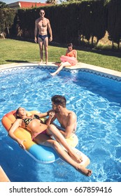 Group of people having time on pool swimming and sunbathing.