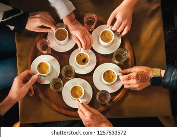 Group of people with henna mehndi tattoo on the hands drinking turkish coffey, top view