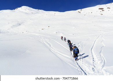 Group of people hiking on snowshoes and mountain snow panorama with blue sky in Stubai Alps, Austria