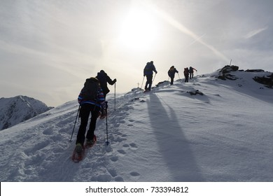 Group of people hiking on snowshoes and mountain snow panorama with summit cross in Stubai Alps, Austria