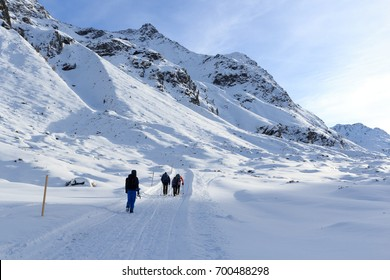 Group of people hiking on wintery snowy path and mountain panorama in Stubai Alps, Austria