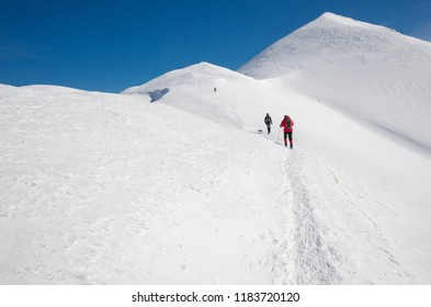 Group of people hiking in Polish Western Tatra mountains during sunny day in winter.
