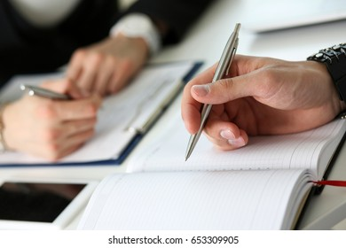 Group of people hold silver pen ready to make note in opened notebook sheet closeup. Training course, university practice homework, school or college exercise, secretary table management concept