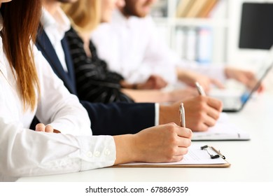 Group of people hold silver pen ready to make note in clipboard pad sheet closeup. Training course, university practice homework, school or college exercise, secretary table management concept