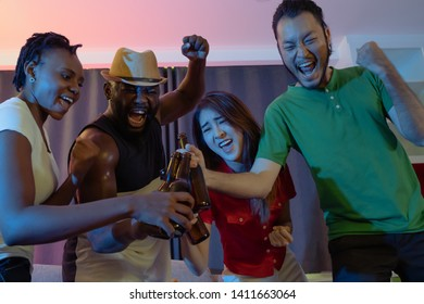 group of people holding beer and wine, party mood of leisure and lifestyle with trendy friends moving and sing song and raised hands up cheers together in night neon light party background