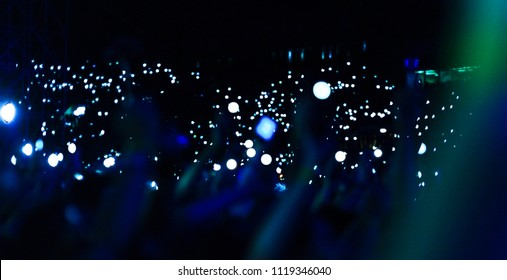 Group of people holding cigarette lighters and mobile phones at a concert crowd of people silhouettes with their hands up. Dark background, smoke, spotlights. Bright lights