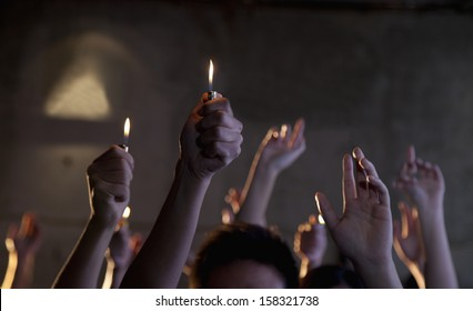 Group of people holding cigarette lighters at a concert