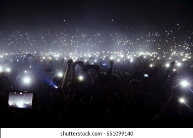 Group of people holding cigarette lighters and mobile phones at a concert
