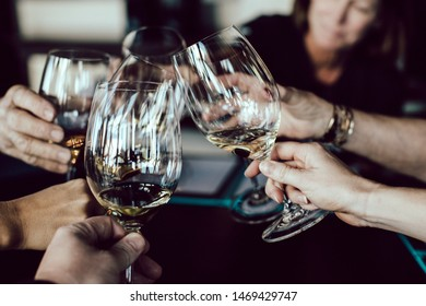 group of people holding footed glasses