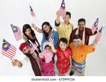 Group of people holding Malaysia flag, posing at camera