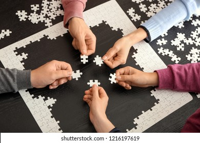 Group of people holding pieces of puzzle over dark table