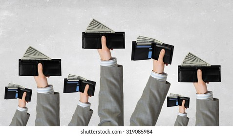 Group of people holding wallets with cash in raised hands