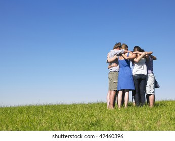 A group of people huddle in a field. Horizontally framed shot.