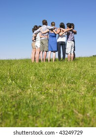 A group of people huddle in a field. Vertically framed shot.