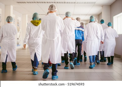 group of people in industrial production. people go back to the camera in white gowns and shoe covers are on the factory tour