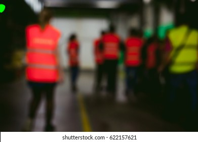 group of people in industrial production. people go back to the camera in Overalls  on factory tour. abstract background blur