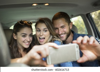 A group of people inside a car, two women and a man taking a selfy