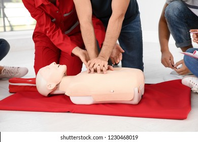 Group of people with instructor practicing CPR on mannequin at first aid class indoors, closeup