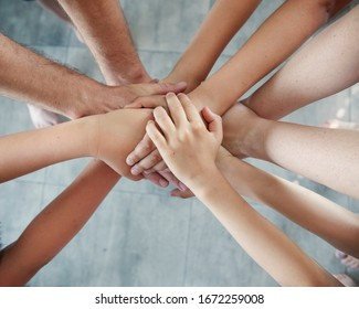 group of people joining hands, success in teamwork