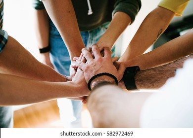 Group of people joining hands together. College students teamwork stacking hands. Young entrepreneurs brainstorming on the new ideas. Teamwork unity and solidarity. Business cooperation.